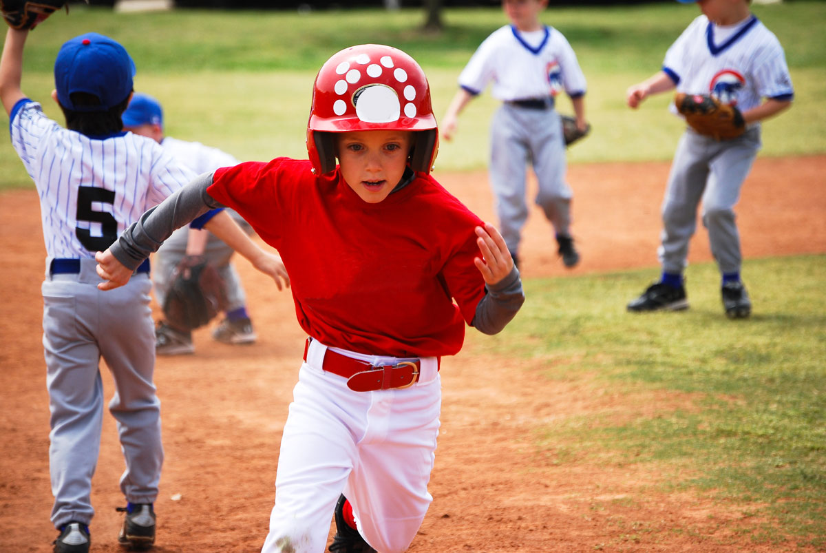 young child in red baseball outfit running the bases