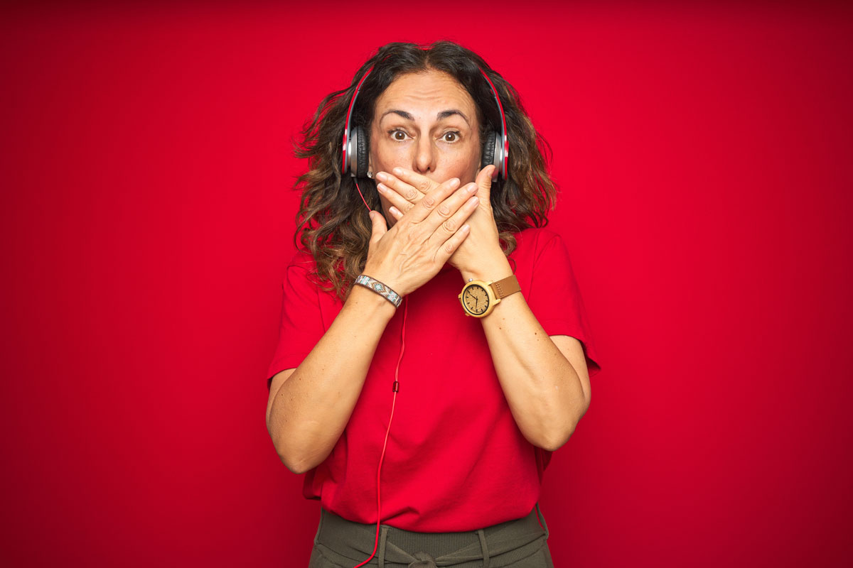 women with headphones on, in front of red background, with hands over her mouth as if she said the wrong thing