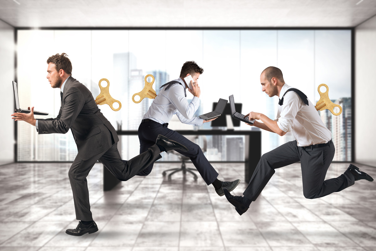 Business people running around the office with winding keys on their backs in a frantic mood