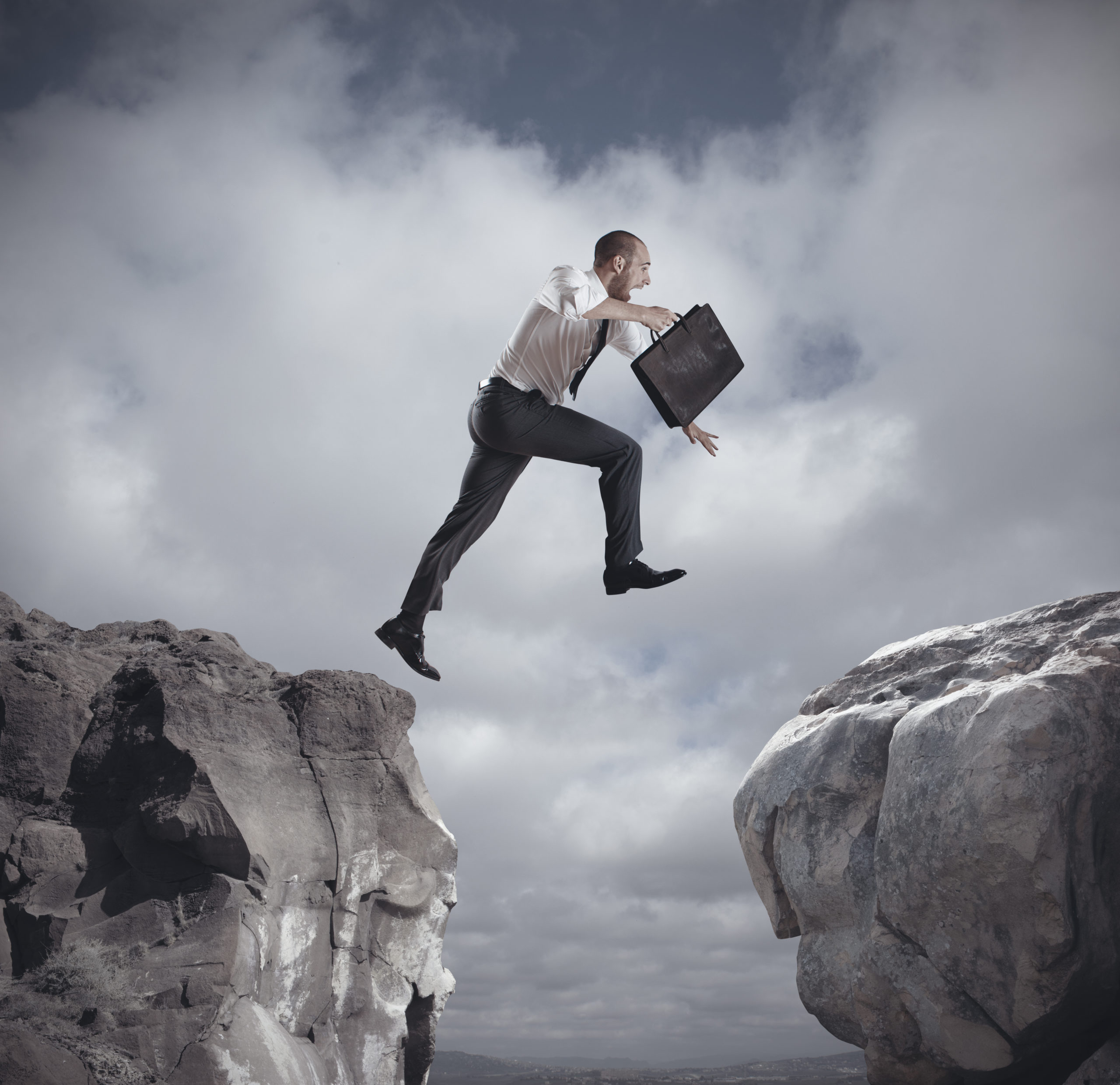 business man jumping over a cliff from one side to another while holding a brief case